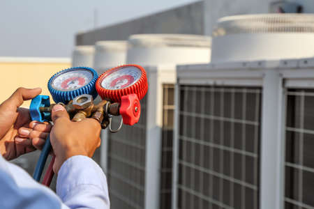 Technician using manifold gauge is measuring equipment for filling industrial factory air conditioners after cleaning and checking for maintenance outdoor air compressor unit.