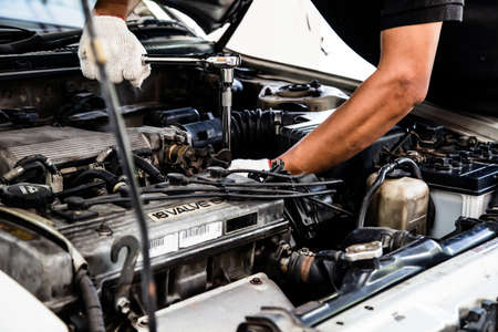 Close-up hands of auto mechanic are using the wrench to repair a car engine in auto car garage. Concepts of car care fixed repair and services.