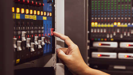 Close-up hand adjust the volume on sound mixer in studio workplace for live the media and sound recording equipment and sound system concept. Standard-Bild