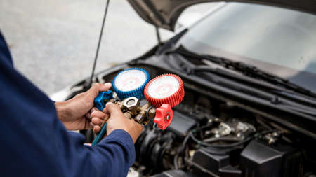 Auto mechanic are using measuring equipment tool for filling car air conditioners. Concepts of car care fix checking repair service and insurance.