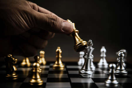 Close up hand choose gold chess to fight with silver chess team on chess board Concept of business strategic plan and professional teamwork and challenge management.