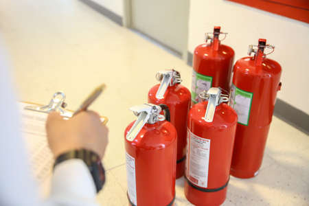 Fire fighter are checking the red fire extinguishers tank in the building concepts of fire prevention emergency and safety rescue of fire services and training. Standard-Bild - 157280436