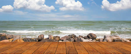 Wooden floor for the beach walkway with a rocky sea background blue sky and cloud. Standard-Bild - 157280376