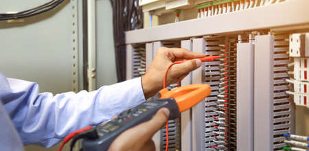 Electrical engineer using measuring equipment to checking electric current voltage at circuit breaker and cable wiring system for maintenance in main power distribution board. Standard-Bild - 157280595