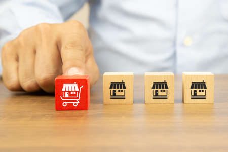 Close-up hand chooses cube wooden toy blocks stack with franchise business store icon in the shopping cart. Concepts of online e-marketplace or e-commerce franchising to growth and branch expansion strategy of financial marketing planning. Archivio Fotografico