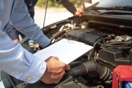 Auto mechanic using checklist for car engine systems after fixed. Concepts of car fix and checking repair and service maintenance.