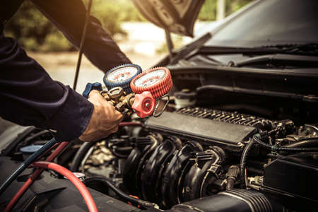Close up hand of auto mechanic are to use manifold gauge is measuring equipment for filling car air conditioners. Concepts of car care fix checking repair service and insurance. Stock Photo