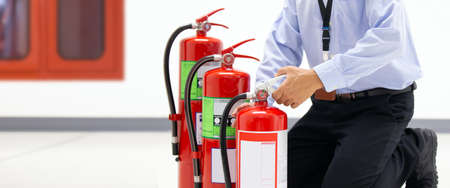 Office man checking the handle of the red fire extinguishers tank in the building concepts of prevent case for emergency and safety rescue and fire training.