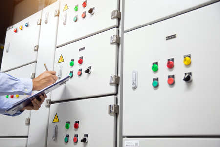 Electrical engineer checking  air handling unit (AHU) starter control panel for air conditioner or load center cabinet or consumer unit for maintenance and check the electric current voltage  in main power distribution room. Reklamní fotografie