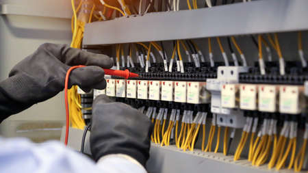Close-up hand of electrical engineer using measuring equipment to checking electric current voltage at circuit breaker and cable wiring system for maintenance in main power distribution board.