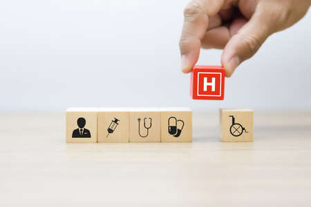 Wooden toy blocks stacked with medical and health icons. Standard-Bild