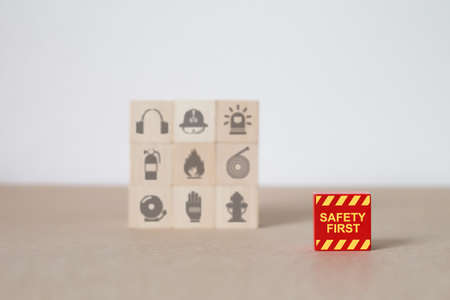 Wooden toy blocks stacked with safety icons.