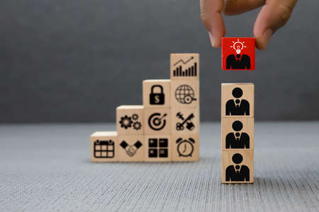 Wooden toy blocks stacked with business human resources. Standard-Bild