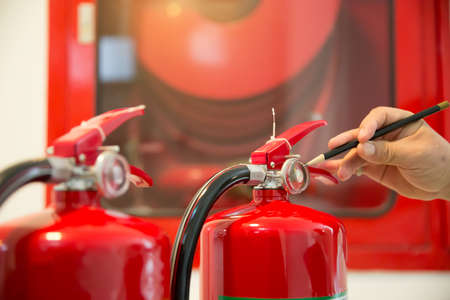 Engineer checking Fire extinguisher.