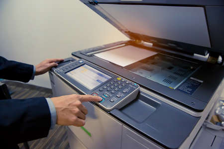 Businessmen are using the photocopier.