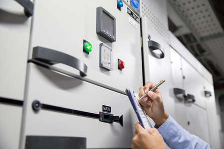 Electrical engineer checking electric current voltage at circuit breaker of air handling unit (AHU) starter control panel for air conditioner or load center cabinet for maintenance in main power distribution room.
