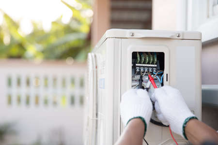 Close up hand of technician using measuring equipment to checking electric current voltage at circuit breaker on outdoor air compressor unit after installation and air conditioner services maintenance Standard-Bild
