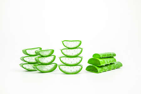 Pile of fresh aloe vera plant slices stacked and aloe vera stalk or leaves with water dropping isolate on white background.