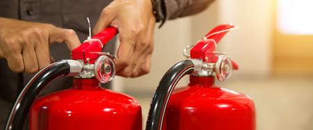 Firefighter checking the safety pin at the handle of the red fire extinguishers tank in the building concepts of prevent case for emergency rescue and fire training.
