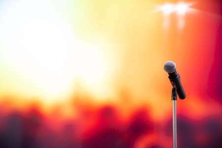 Public speaking backgrounds, Close-up the microphone on stand for speaker speech presentation stage performance with many people blur and bokeh light background.