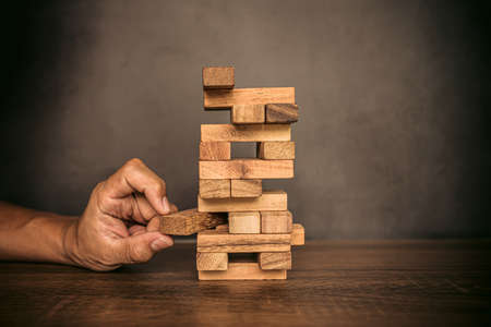 Close-up hand pull wooden block from other the wood block stacked in tower shape concepts of financial risk management and strategic planning. Standard-Bild