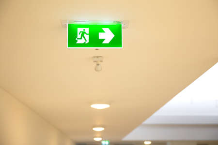 Close up the green emergency fire exit sign or fire escape on the building ceiling for doorway or door exit concepts for evacuation in the event of a fire.