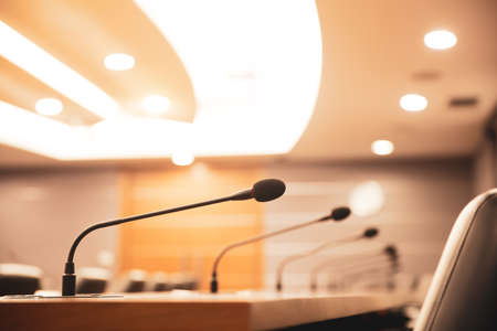 Close up the conference microphone on the meeting table or board room for speaker and workshop presentation concepts
