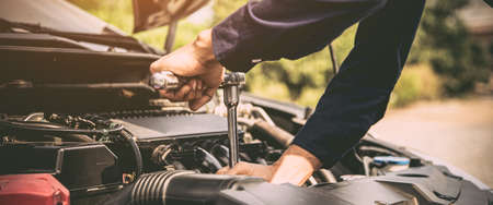 Close-up hands of auto mechanic are using the wrench to repair and maintenance auto engine is problems at car repair shop. Concepts of car care check and fixed and services insurance.