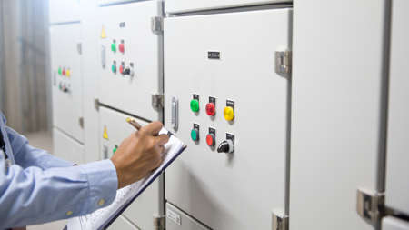 Electrical engineer checking electric current voltage at circuit breaker of air handling unit (AHU) starter control panel for air conditioner or load center cabinet for maintenance in main power distribution room. Standard-Bild