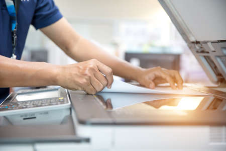 Close up hand of office man is press button on panel and put paper on the copier machine in copy room for scanning document printing a sheet and photocopy.
