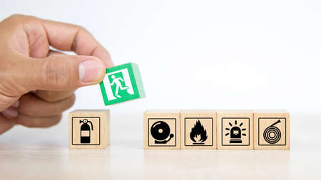 Close-up hand choose a wooden toy blocks stacked with fire exit icon for fire safety protection concepts.