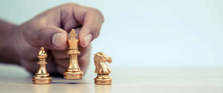 Close-up hand chooses king chess standing with a team on chess concepts of business team and leadership strategy and organization risk management or strategic plan and professional teamwork.