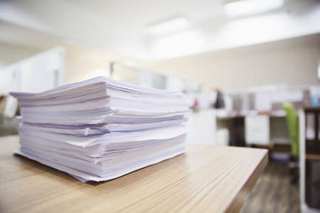 Pile of unfinished documents or reuse paperwork on office desk stacked concepts of reduce recycle and messy desk.