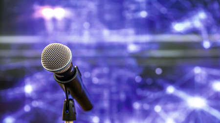 Public speaking backgrounds, Close-up the microphone on stand for speaker speech presentation stage performance with blur and bokeh light background. Reklamní fotografie