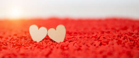 Close-up two hearts shape on a red sand background with the sun shines and shadows. Concept the day of love 14 February happy valentine's day.