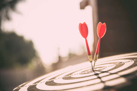 Close-up the bullseye target or dart board has red dart arrow throw hitting the center of a shooting with the sun shines and shadows for business targeting and winning goals business concepts Reklamní fotografie
