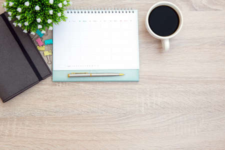 The top view desk and blank calendar with a pen and office equipment for working area copy space composition and work from home concepts.