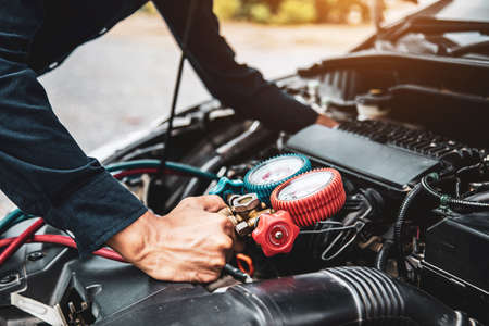 Close up hand of auto mechanic are to use measuring manifold gauge for filling car air conditioners. Concepts of fix and checking for repair service and car insurance.