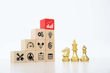 Cube wooden toy block stacked with business icon and chess standing concepts of business team strategic planning to growth and organization management. Reklamní fotografie