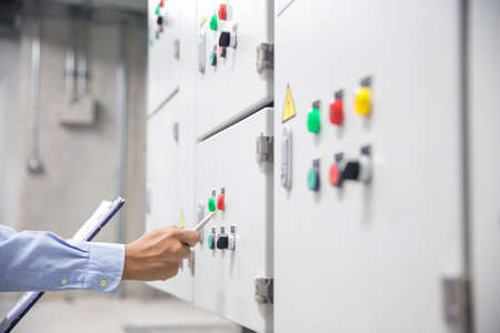 Electrical engineer checking electrical voltage at circuit breaker air handling unit (AHU) starter control panel for air conditioner load center cabinet for maintenance power system distribution. Reklamní fotografie
