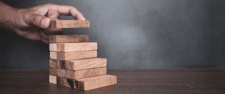 Close-up hand is placing wood block tower stacked in pyramid shape with caution to prevent collapse or crash concepts of financial risk management and strategic planning.