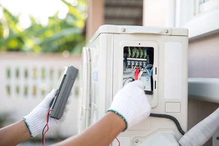 Close up technician hand using measuring equipment checking electric current voltage at circuit breaker on outdoor air compressor unit after installation and air conditioner services maintenance Reklamní fotografie