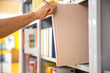 Close up hand picking a book from bookshelf in the library. Concepts for reading textbook and school for student knowledge education.
