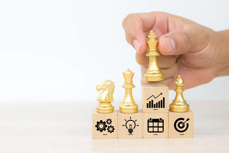 Hand choose king chess on wooden toy blocks stacked with graph icon concepts of business team strategic planning to growth and organization management.