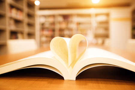 Close up page of a book in heart shape on the table at library room of lifestyle love to read and reading a text book and February valentine day concepts.