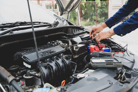 Close up hand of auto mechanic are using measuring equipment tool for checking car battery. Concepts of car fix repair and service maintenance.