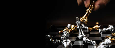 Close up hand choose the king gold chess to fight with silver team on chess board. Concept of business team and leadership and strategic plan challenge management. Reklamní fotografie