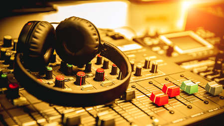 Close-up headphone and audio mixer in studio for sound control system and recording equipment and music instrument.