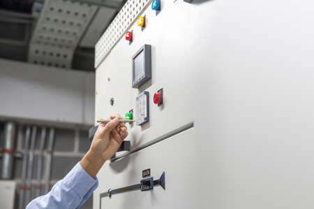 Close-up hand of electrical engineer using a pen to reset and checking electric current voltage at circuit breaker cabinet and cable wiring for maintenance in main power distribution board.