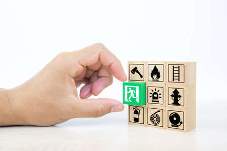 Close-up hand choose wooden toy blocks stacked with door exit sing icon with fire extinguisher and fire protect symbol for safety prevent and protection is accident concepts.